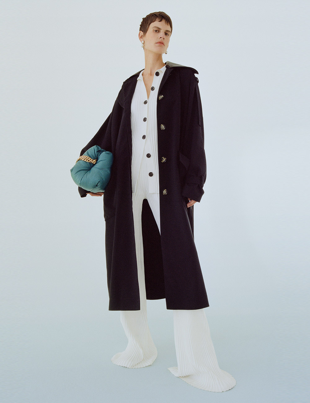 SS21 Look 6: Black Coat with white knit top and pant with blue bag